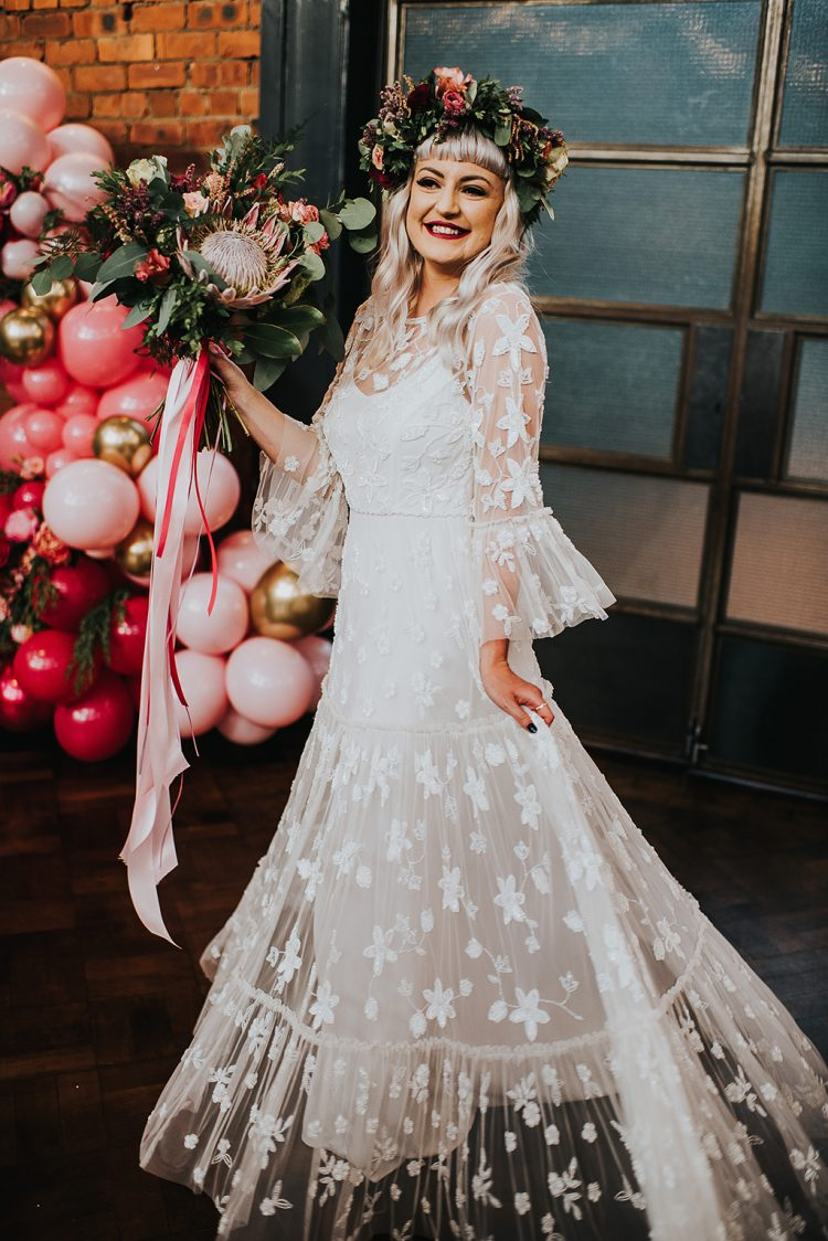 a lace applique A-line wedding dress with an illusion neckline and bell sleeves plus a bold floral crown for a more boho feel