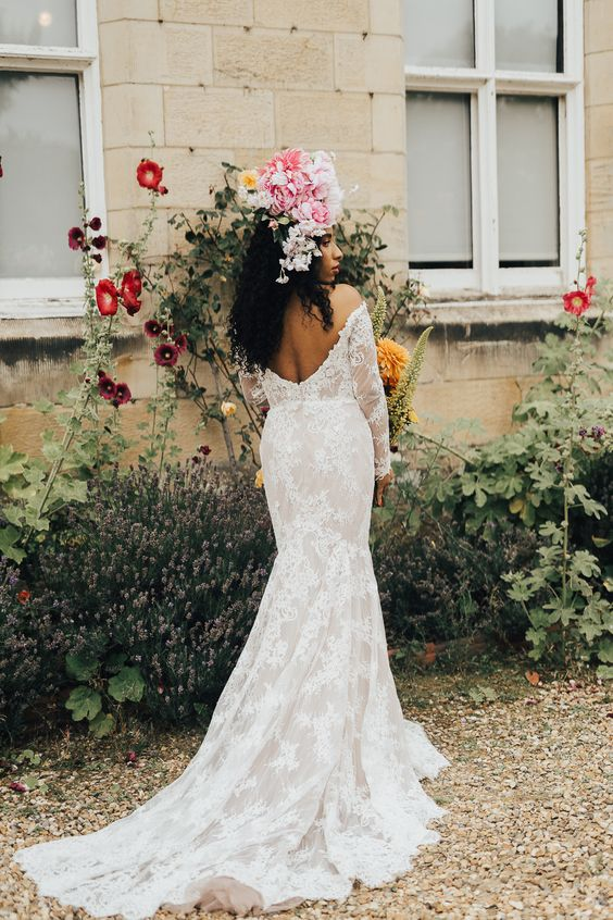 a lace mermaid off the shoulder wedding dress with an open back and long sleeves plus a train for a boho bride