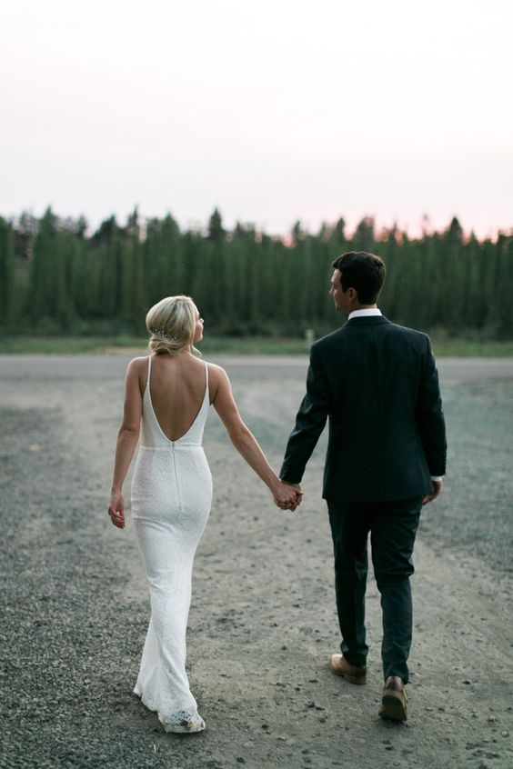 a lace sheath wedding dress with a halter neckline, a low back is ideal for a modern yet romantic bride