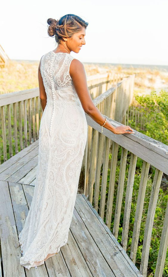 a lace sheath wedding dress with no sleeves, a high neckline and a back on buttons for a beautiful and simple look