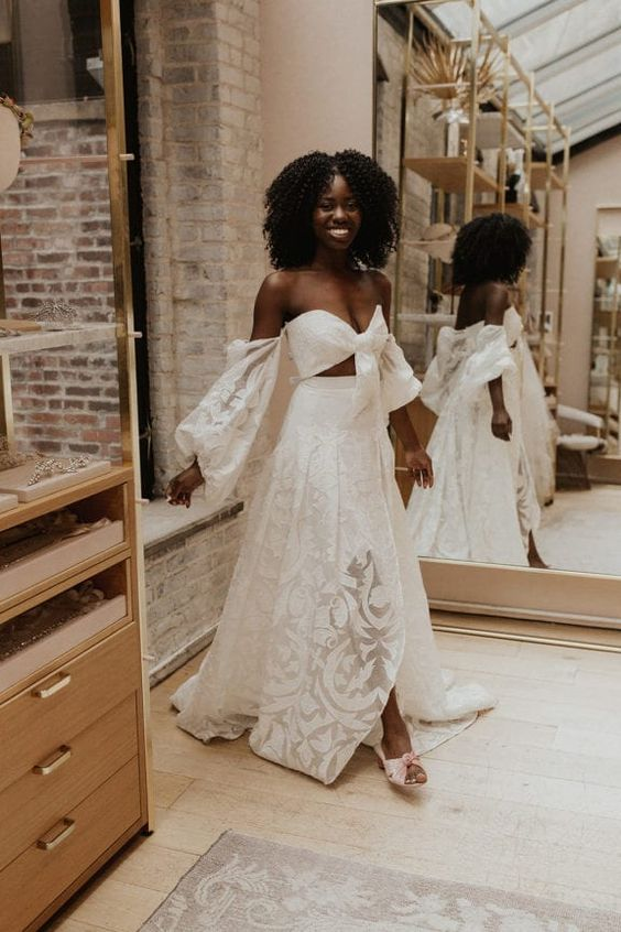 a lace two piece wedding dress wiht a crop top with long sleeves and a pleated maxi skirt with a train for a boho bride