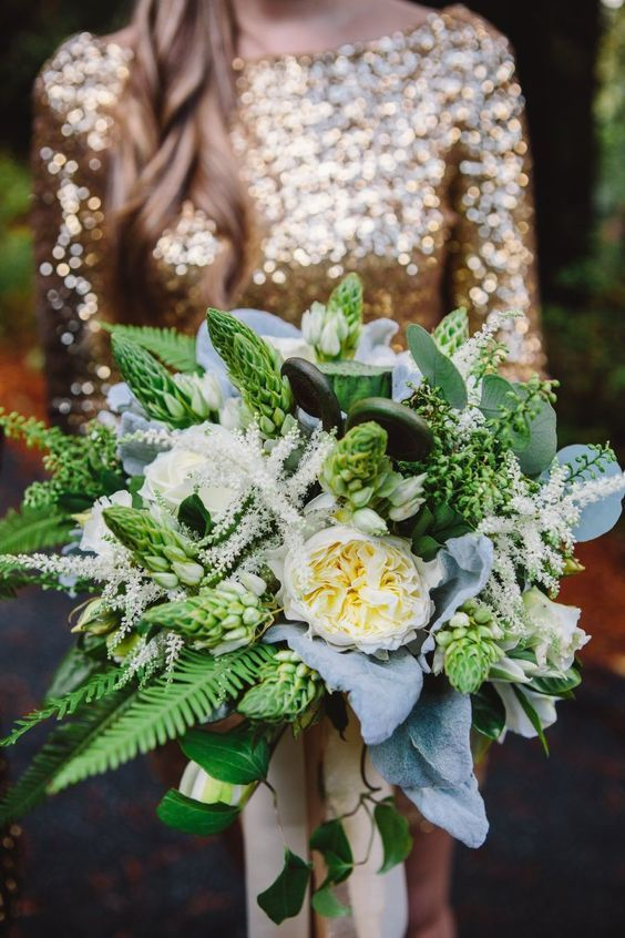 a lovely and dimensional wedding bouquet of various types of greenery and white blooms and pale leaves for a woodland wedding