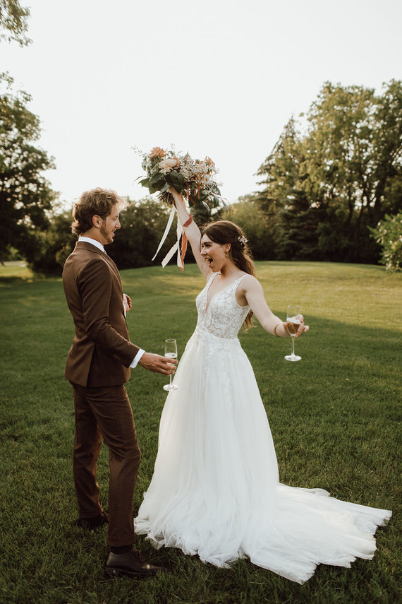 a lovely modern A-line thick strap wedding dress with a lace bodice and a plunging neckline plus a train for a modern chic bride