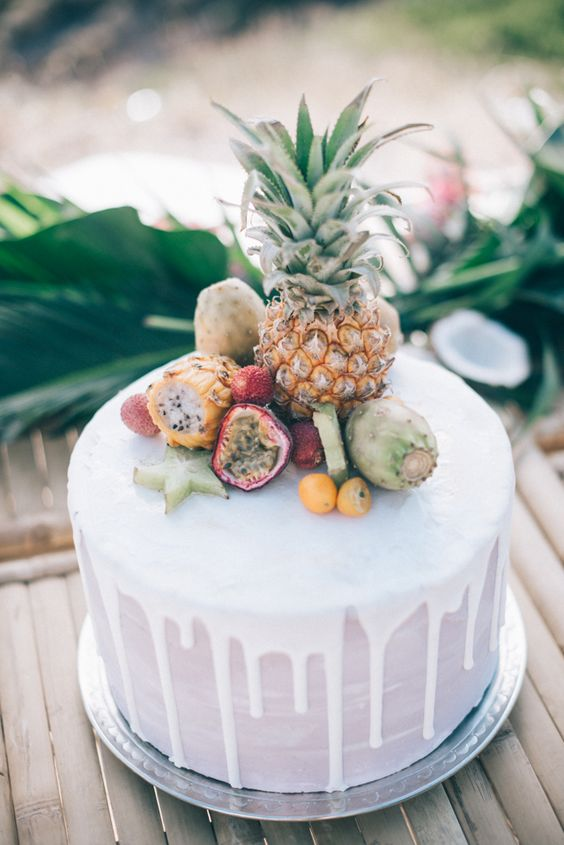 a lovely white wedding cake with drip, fresh tropical fruits including a pineapple is a beautiful and delicious option