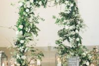 a lush wedding arch decorated with greenery and white blooms and surrounded with candle lanterns