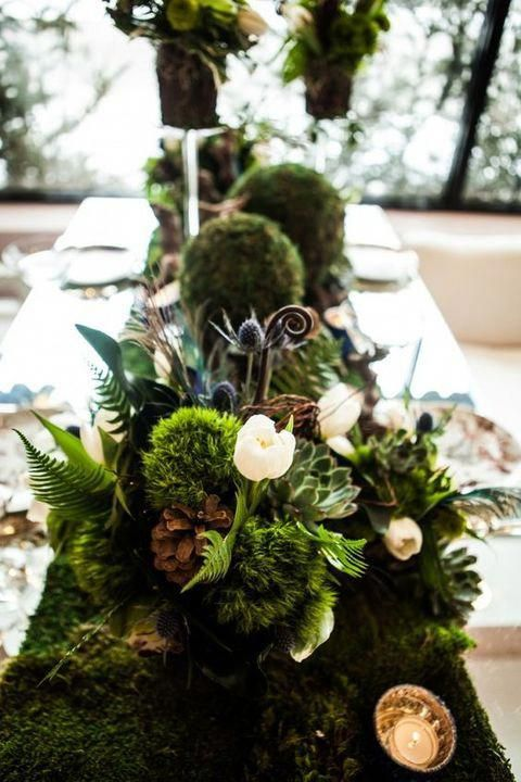 a lush woodland wedding centerpiece of moss, greenery, succulents, pinecones and white blooms plus candles