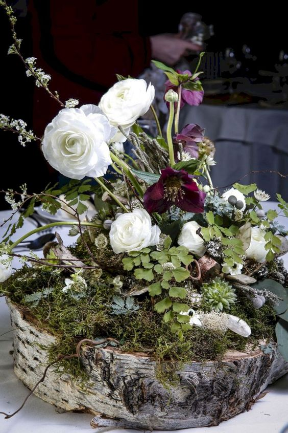 a lush woodland wedding centerpiece with moss, deep purple and white blooms and greenery