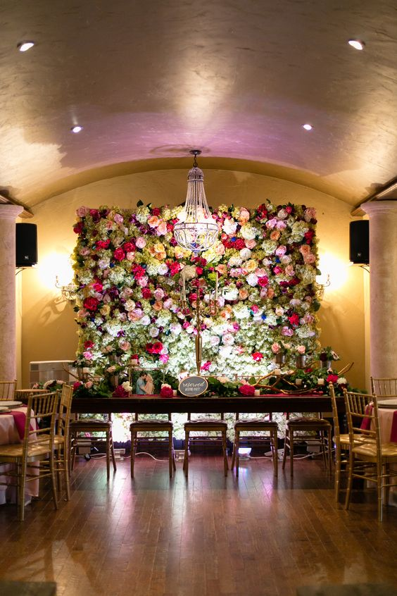 a luxurious bright floral wall is a gorgeous backdrop and a refined chandelier highlights it veyr much