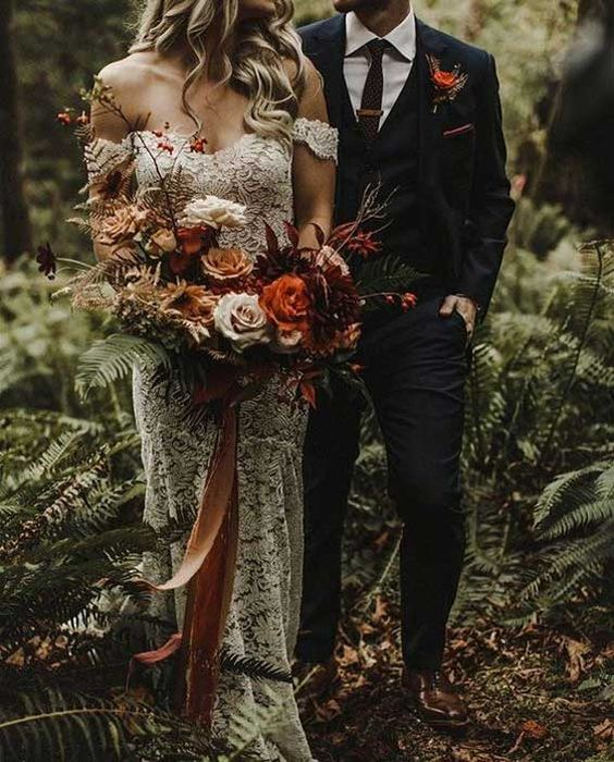 a luxurious moody woodland wedding bouquet of orange, burgundy, creamy and coffee blooms, branches with berries and long ribbons