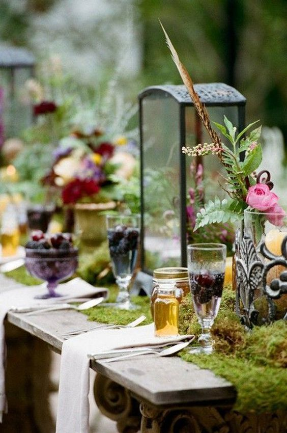 a luxurious woodland wedding tablescape with a moss runner, blooms, berries, feathers and candle lanterns