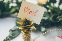 a mini gold pineapple with a card is a chic and stylish idea for a modern tropical wedding