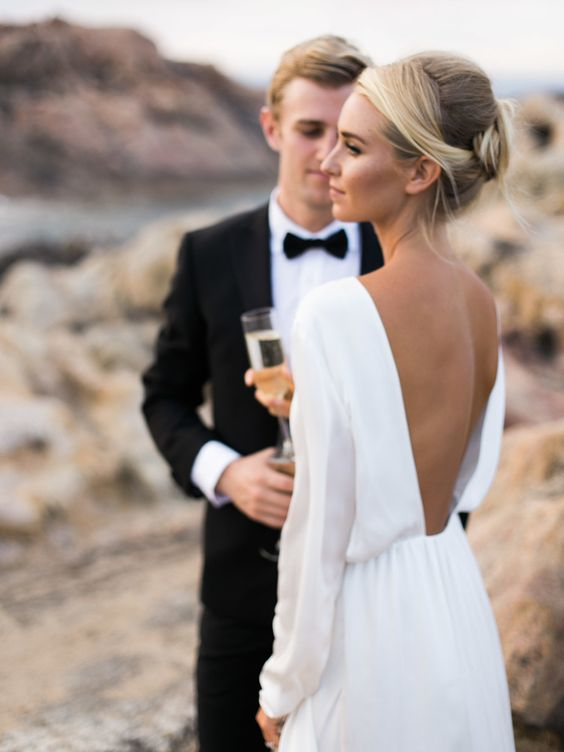 a minimalist A-line plain wedding dress with a low back, long sleeves and a pleated skirt is a very refined and chic idea