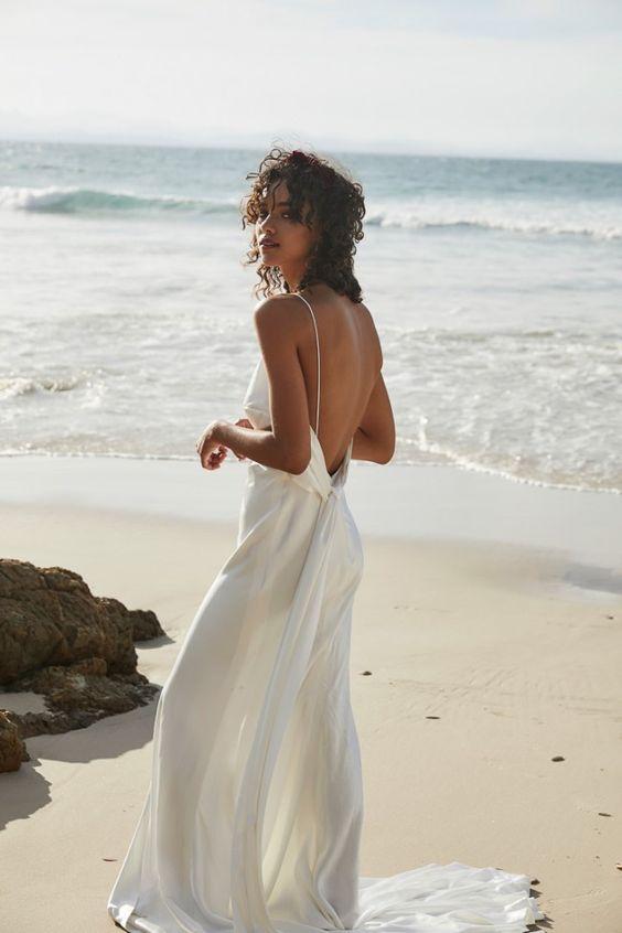 a minimalist flowy wedding dress with spaghetti straps and a sash plus a train for a modern or minimalist beach bride