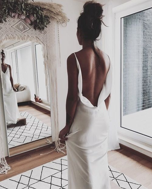 a minimalist plain sheath wedding dress with a low flowy back on straps and a train is pure perfection