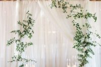 a minimalist wedding altar – a white platform, candles, greenery hanging on curtains