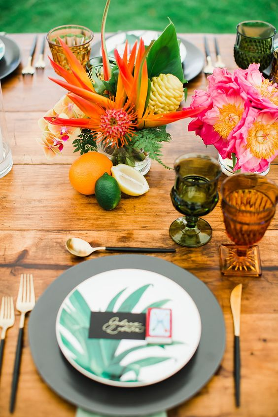 a modern bold tropical wedding table with colored glasses, tropical leaf plates, colorful blooms and fruits