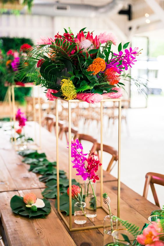 a modern colorful wedding tablescape with a leaf runner, bold blooms on tall stands and mini pineapples
