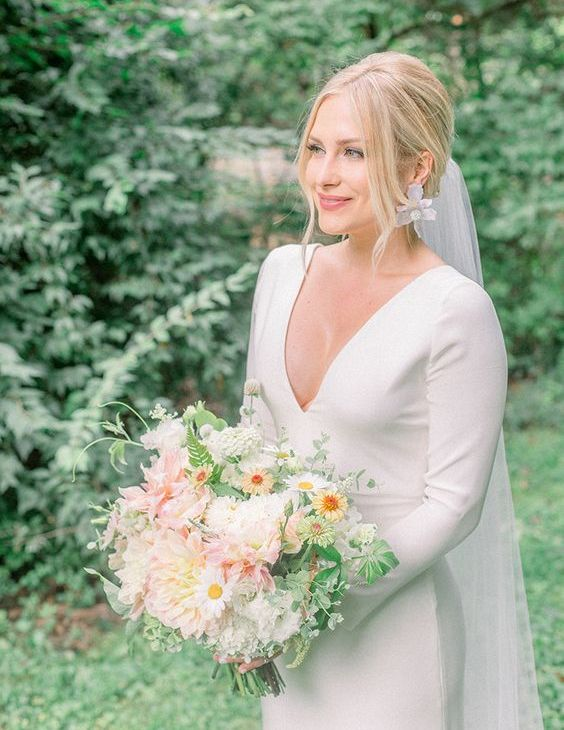 a modern plain fitting wedding dress with a deep V-neckline and long sleeves plus statement earrings and a veil