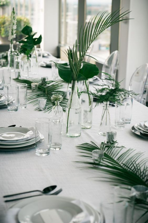 a modern tropical wedding tablescape with ferns and fronds, white porcelain and clear glass