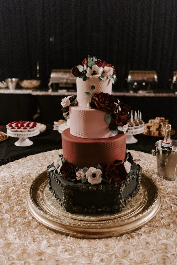 a moody vintage wedding cake in pink, burgundu and black, with floral patterns and lots of sugar blooms