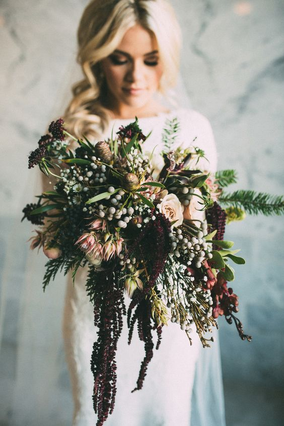 a moody woodland wedding bouquet of deep purple blooms, berries, feathers and pink blooms is all cool