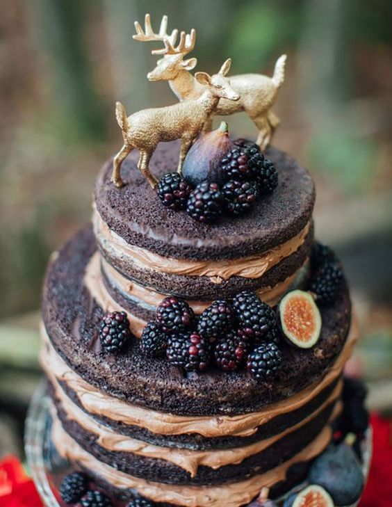 a naked chocolate wedding cake with blackberries, figs and gilded deer toppers for a woodland wedding
