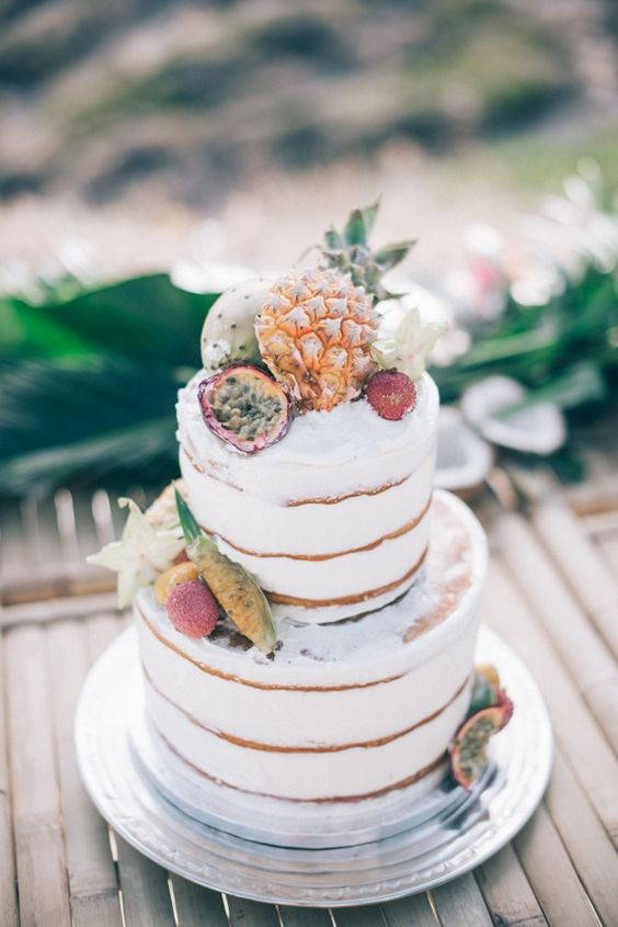 a naked wedding cake topped with fresh tropical fruits is a lovely and chic idea for a modern tropical wedding