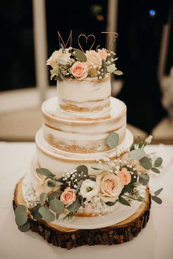 a naked wedding cake with white and blush blooms, baby's breath, foliage and wire toppers