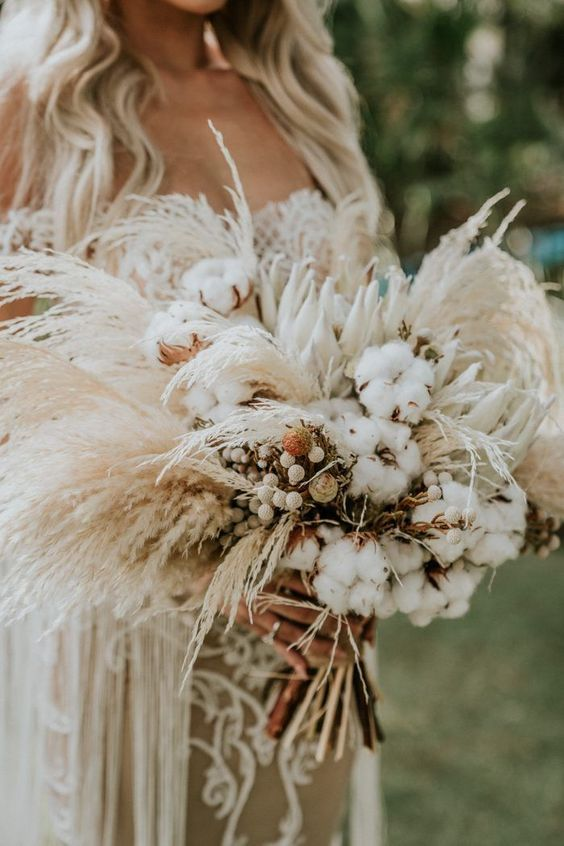 a neutral boho wedding bouquet of cotton, white proteas, berries, pampas grass and spikes