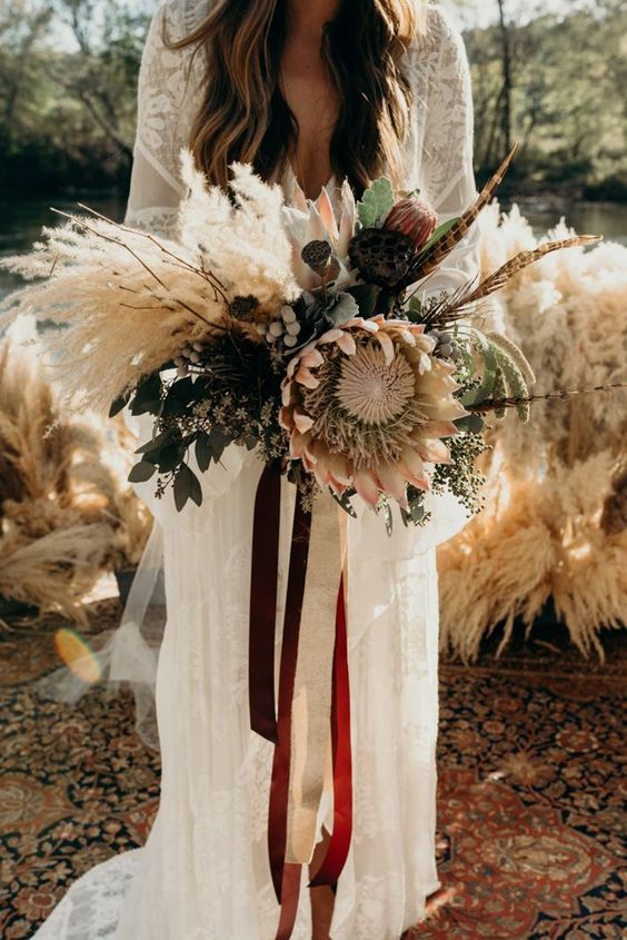 a neutral boho wedding bouquet of dried elements, feathers, berries, eucalyptus, king proteas and twigs