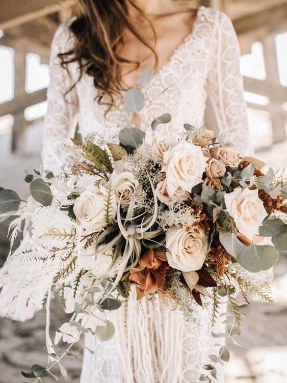 a neutral boho wedding bouquet of white and blush flowers, air plants, sucuclents, eucalyptus for a beach bride