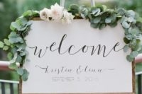 a neutral wedding sign with wooden framing and greenery and neutral blooms is a simple and stylish idea