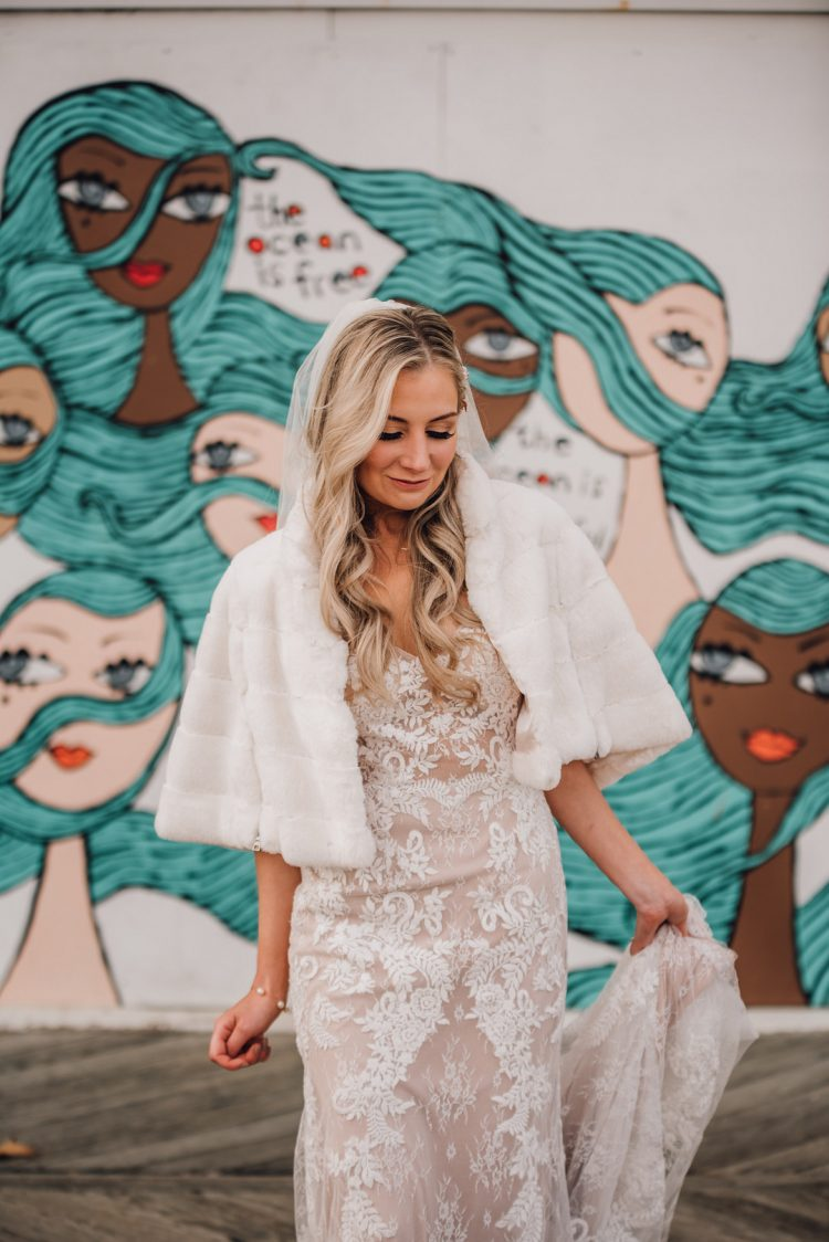 a nude and white lace sheath wedding dress with a train and a white faux fur coverup for a modern glam bride