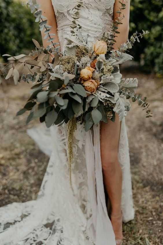a pale boho wedding bouquet of pale greenery, rust blooms, leaves for a summer or fall bride