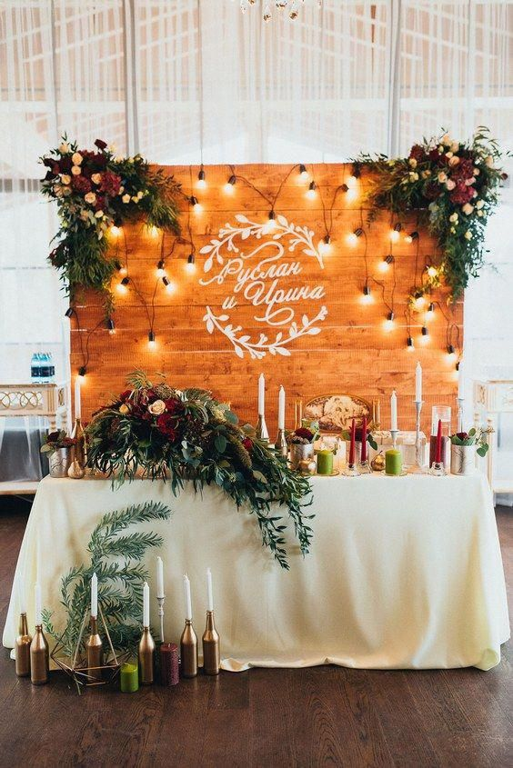 a pallet backdrop with lights, greenery and bright blooms and your couple's names on the wall