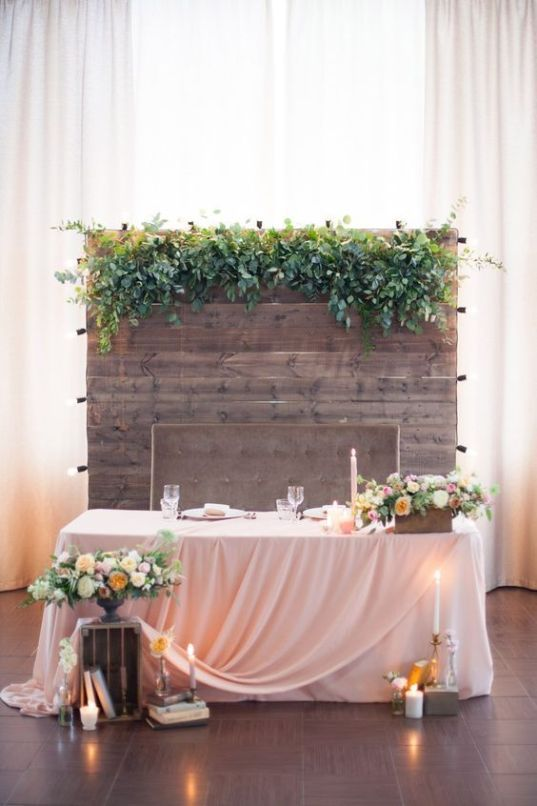 a pallet wooden backdrop with fresh greeneryon top is a cool rustic idea