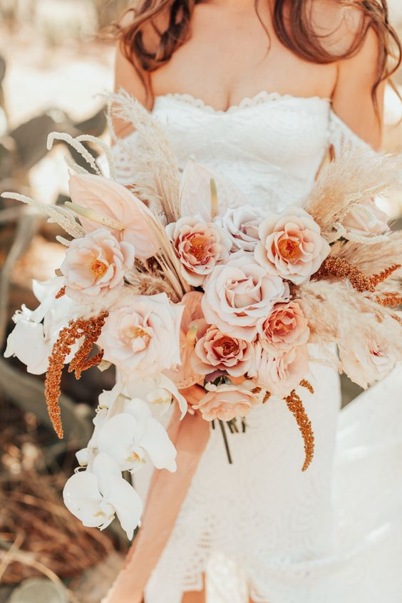 a pastel boho wedding bouquet in blush, light pink, white, with pampas grass and pink ribbons hanging down
