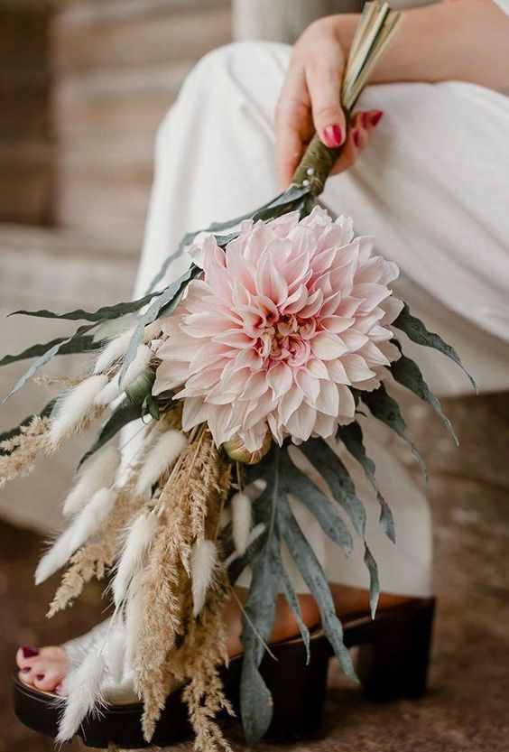 a pastel boho wedding bouquet of a large blush bloom, dried spikes and pale palm leaves