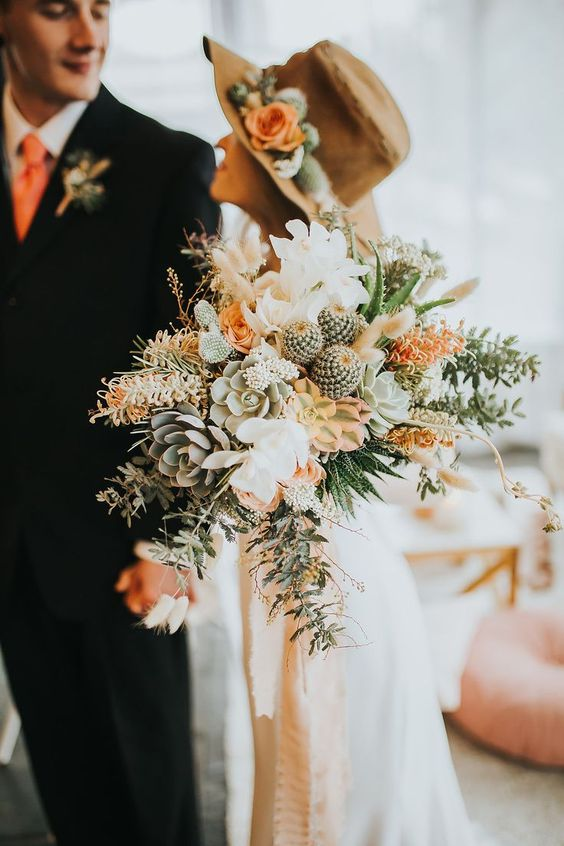 a pastel boho wedding bouquet of succulents, cacti, rust blooms, greenery and leaves for a desert bride