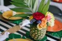 a pineapple vase with a large frond and bold blooms for a bold and fun tropical wedding tablescape