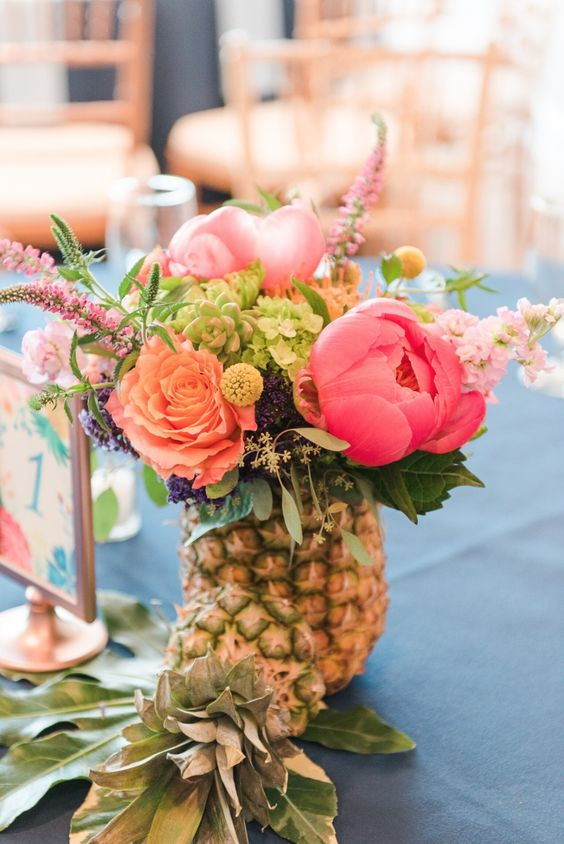 a pineapple vase with bold blooms and greenery is an ideal option for a modern and bright tropical wedding