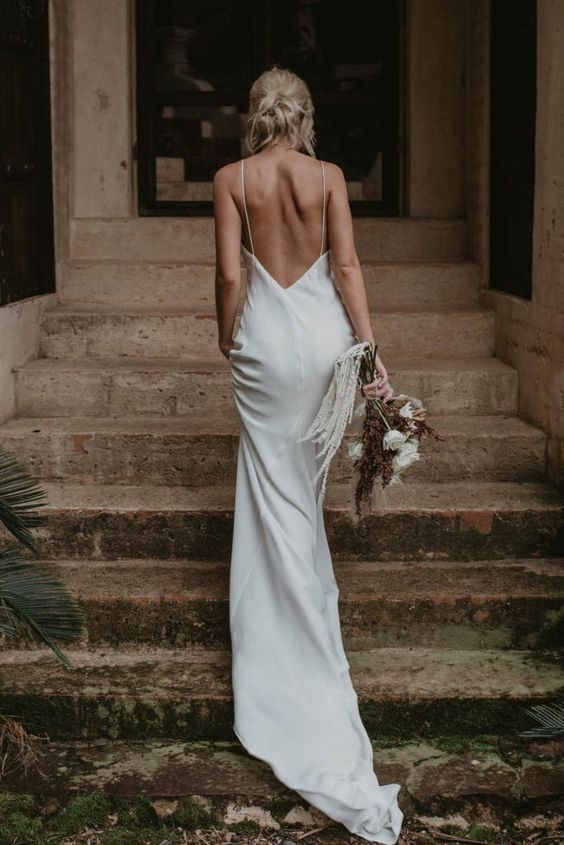 a plain flowy wedding dress with spaghetti straps and a train plus a low back is a perfect idea for a modern summer bride