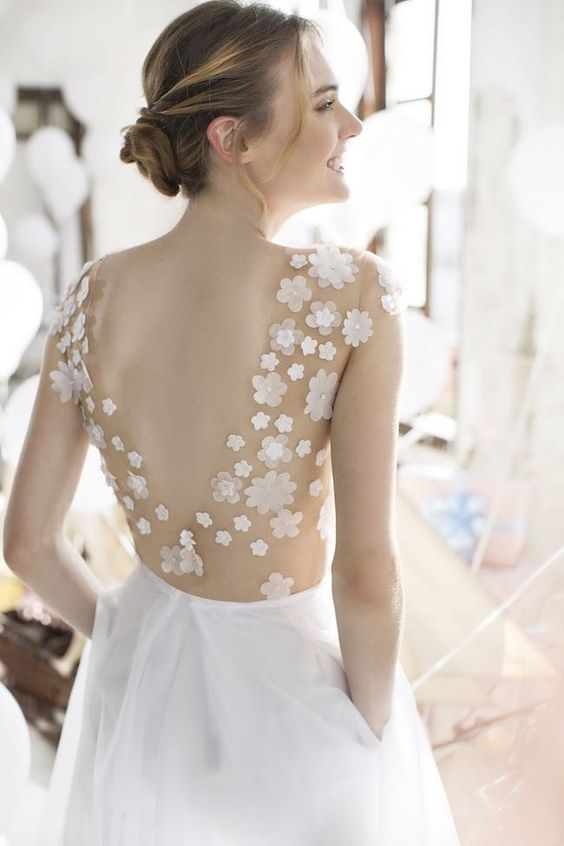 a pretty A-line wedding dress with a sheer bodice with floral appliques and a plain skirt with pockets and a low back is very chic