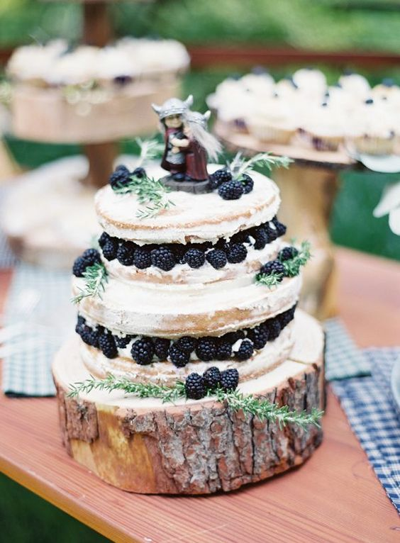 a quirky woodland wedding cake, a semi naked one with greenery, berries and fun Viking toppers
