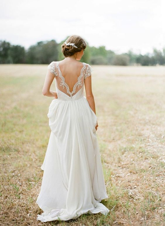 a refined A-line wedding gown with a lace bodice, a low back with cap sleeves and a pleated plain skirt with a train