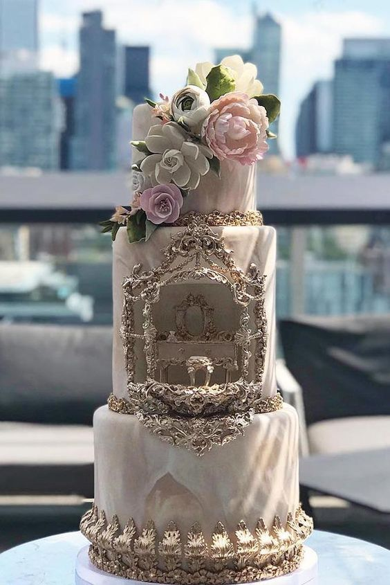 a refined and chic vintage wedding cake with gold detailing, a watercolor design and blush and white sugar blooms