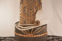 a refined art deco wedding cake in black, white and gold, with geometric patterns, beads and feathers