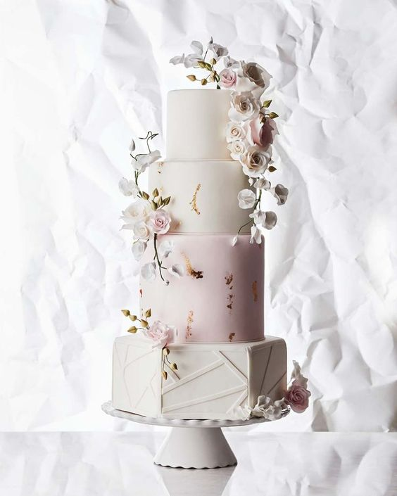 a refined blue and white wedding cake with gold leaf decor, sugar blush and white blooms is a very chic idea