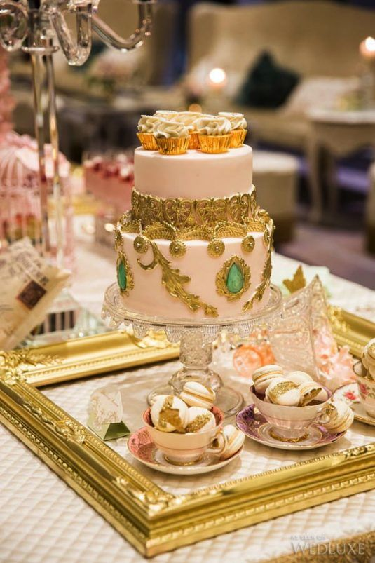 a refined blush wedding cake with gold detailing and green rhinestones is a very sophisticated idea