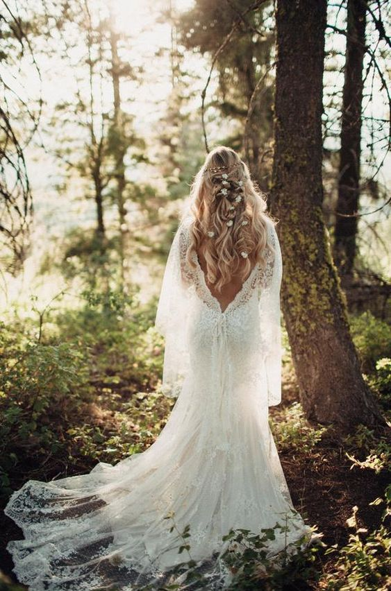 a refined lace A-line wedding dress with a low back, long sleeves, a capelet and a train for a forest nymph is very beautiful